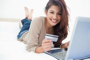 A woman smiling while looking at her credit history