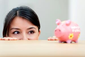 Beautiful woman looking at her savings in a piggybank-1